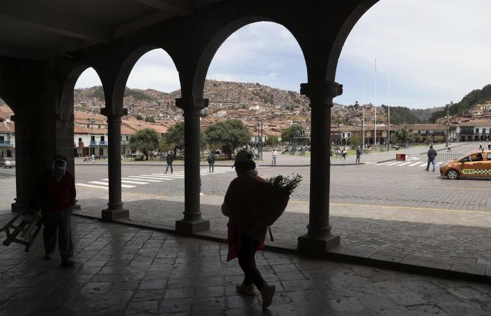 A woman carries herbs in the Plaza de Armas in downtown Cusco, Peru, Thursday, Oct. 29, 2020. All major sites around Cusco are currently open for free, in hopes of sparking any tourism after the COVID-19 pandemic brought it to a standstill. (AP Photo/Martin Mejia)