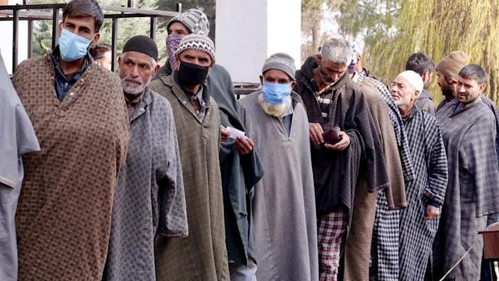 Voters wait in a queue during polling in Shopian.