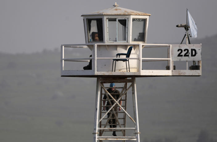 A U.N. peacekeeper from the UNDOF force walks up to a watch tower at the Quneitra Crossing between Syria and the Israeli-controlled Golan Heights, Saturday, March, 9, 2013. (AP Photo/Dan Balilty)