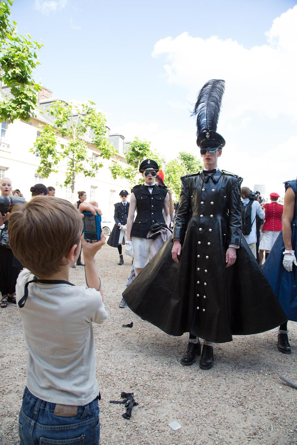 """<div class=""""caption-credit""""> Photo by: Victor Boyko/Getty Images</div>A brave child photographs yet another member of the Thom Browne militia. This one has wings, which probably means he's important. <br>"""