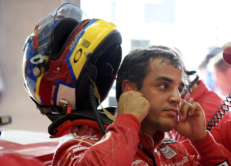 Driver Juan Pablo Montoya takes his helmet off after a practice session for Sunday's NASCAR Sprint Cup series auto race at Atlanta Motor Speedway in Hampton, Ga., Friday, Aug. 30, 2013. (AP Photo/Dave Tulis)