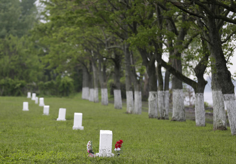 FILE - This May 23, 2018, file photo, shows graves marked by white markers on Hart Island in New York. New York City's mayor signed a bill on Wednesday, Dec. 4, 2019, that transfers control of the nation's largest public burial ground from the correction department to the parks department. (AP Photo/Seth Wenig, File)