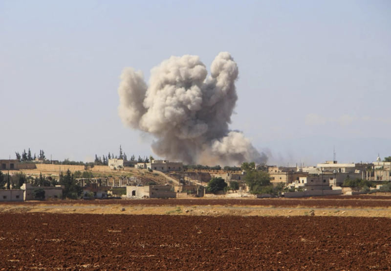 This photo released on Monday, Sept. 10, 2018 by the Syrian Civil Defense group known as the White Helmets, shows smoke rising from a Syrian government airstrike, in Hobeit village, near Idlib, Syria. High-level diplomats from Iran, Russia and Turkey were meeting Tuesday with the U.N. envoy for Syria about creating a committee to revise the war-battered country's constitution. Tuesday's talks in Geneva under U.N. envoy Staffan de Mistura come amid concerns he and other U.N. officials have expressed about a looming battle for Idlib. (Syrian Civil Defense White Helmets via AP)