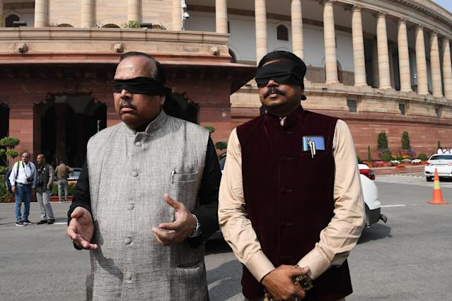 Trinamool Congress (TMC) Members of Parliament Sukhendu Shekhar Roy (L) and Abir Biswas (R) protest against the Union government's response to the Delhi riots, wearing black bands over their eyes, at the Parliament in New Delhi on March 2, 2020. (Photo by Prakash SINGH / AFP) (Photo by PRAKASH SINGH/AFP via Getty Images)