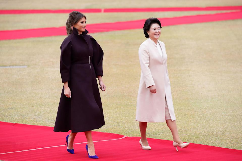 For the Trump trip to South Korea, Melania chose to wear a headline-grabbing maroon coat by Emilio Pucci. [Photo: Getty]