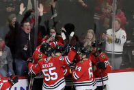 Chicago Blackhawks left wing Alex DeBrincat (12) celebrates with teammates after scoring the game-winging goal against the Nashville Predators during the overtime period of an NHL hockey game in Chicago, Friday, Feb. 21, 2020. (AP Photo/Nam Y. Huh)