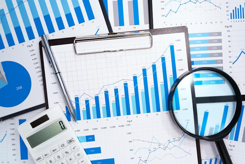 A calculator, pen, and magnifying glass on top of multiple financial charts