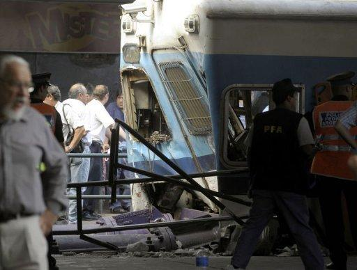 Police and rescue workers surround a train that crashed at Once train station in Buenos Aires. A packed commuter train slammed into a retaining wall at a railway terminus in Buenos Aires during rush hour, leaving at least 49 dead, 550 injured, and dozens trapped in the wreckage
