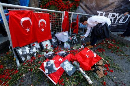 FILE PHOTO: A man places flowers at the entrance of Reina nightclub, which was attacked by a gunman, in Istanbul
