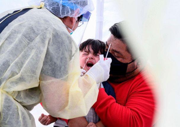 PHOTO: Jose Vatres, right, holds his son Aidin who reacts as nurse practitioner Alexander Panis, left, takes a nasal swab sample to test for COVID-19 at a mobile testing station in a public school parking area in Compton, California, on April 28, 2020. (Robyn Beck/AFP via Getty Images, FILE)