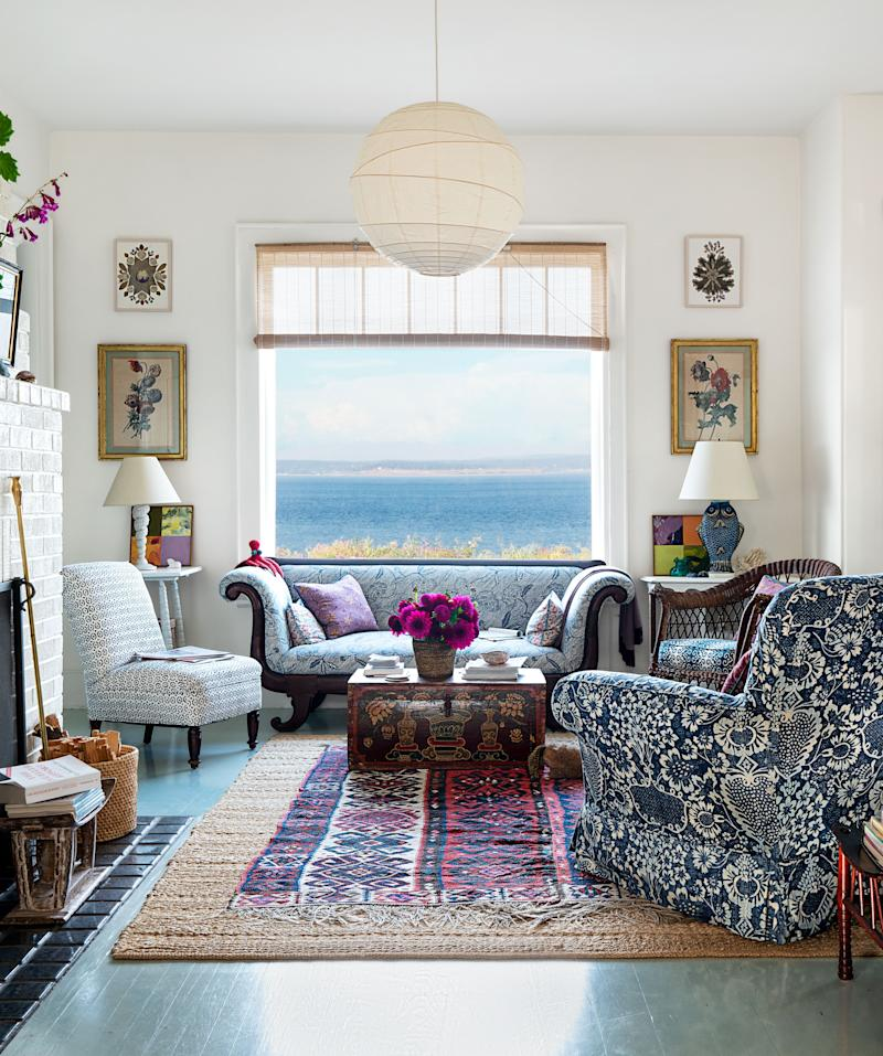 In the living room, a 19th-century American classical sofa is set beside a window offering views of Puget Sound. At left, the antique slipper chair wears a Galbraith & Paul print; 19th-century Tibetan painted traveling trunk.