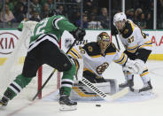 Dallas Stars center Radek Faksa (12) tries to score against Boston Bruins goaltender Tuukka Rask (40) and defenseman Torey Krug (47) in the first period of an NHL hockey game Friday, Nov. 16, 2018, in Dallas. (AP Photo/Richard W. Rodriguez)