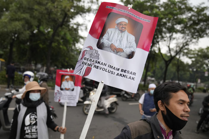 """Supporter holds posters bearing a portrait of firebrand cleric Rizieq Shihab during a rally near the district court where his sentencing hearing is held in Jakarta, Indonesia, Thursday, June 24, 2021. The influential cleric was sentenced to another four years in prison on Thursday for concealing information about his coronavirus test result. Writings on the poster read """"Free our grand imam for moral revolution."""" (AP Photo/Dita Alangkara)"""