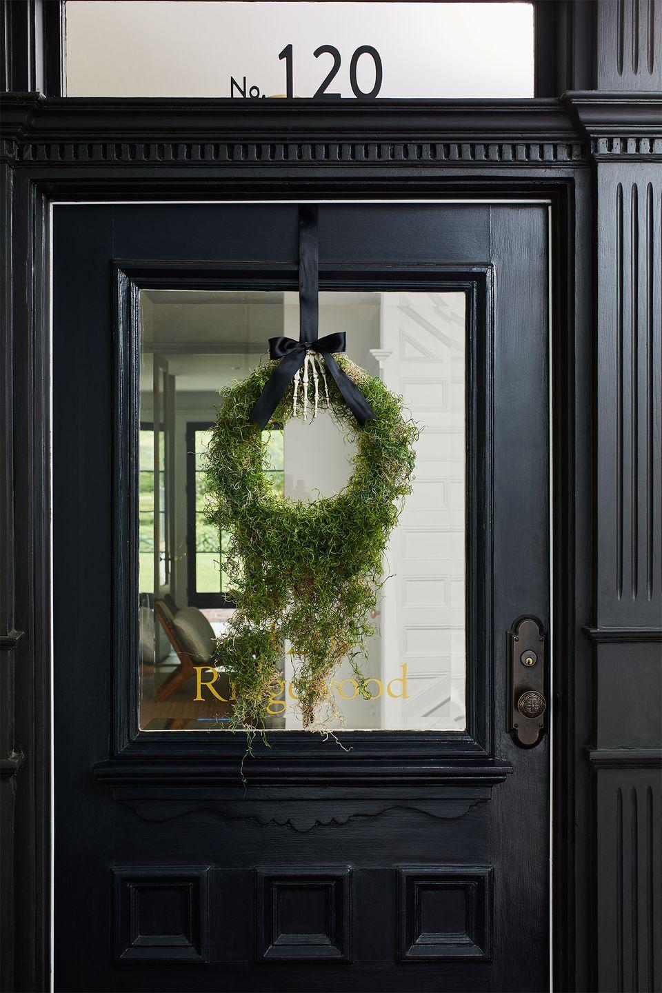 """<p>Take a mossy wreath to the next level by using a plastic skeleton hand and ribbon to hang it from your door. <br></p><p><strong>RELATED:</strong> <a href=""""https://www.goodhousekeeping.com/holidays/halloween-ideas/g79/diy-halloween-wreaths/"""" rel=""""nofollow noopener"""" target=""""_blank"""" data-ylk=""""slk:Scary-Good Halloween Wreaths to Impress Trick-or-Treaters"""" class=""""link rapid-noclick-resp"""">Scary-Good Halloween Wreaths to Impress Trick-or-Treaters</a></p>"""