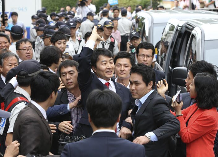 South Korean lawmaker Lee Seok-ki, center, of the leftist Unified Progressive Party waves to his supporters upon his arrival at the Suwon District Court in Suwon, south of Seoul, South Korea, Thursday, Sept. 5, 2013. South Korea's spy agency on Thursday arrested Lee implicated in an allegation of rebellion that has sparked a political firestorm in the country which faces a persistent threat from rival North Korea. The arrest of Lee was made after the court issued a warrant for his detention following hours of review. A day earlier, the country's parliament voted to remove Lee's legislative immunity against his arrest in their first passage of such a motion over rebellion charges. (AP Photo/Yonhap, Kim Ju-sung) KOREA OUT