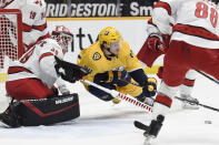 Nashville Predators left wing Tanner Jeannot (84) reaches for the puck in front of Carolina Hurricanes goaltender Alex Nedeljkovic (39) during the second period of an NHL hockey game Saturday, May 8, 2021, in Nashville, Tenn. (AP Photo/Mark Zaleski)