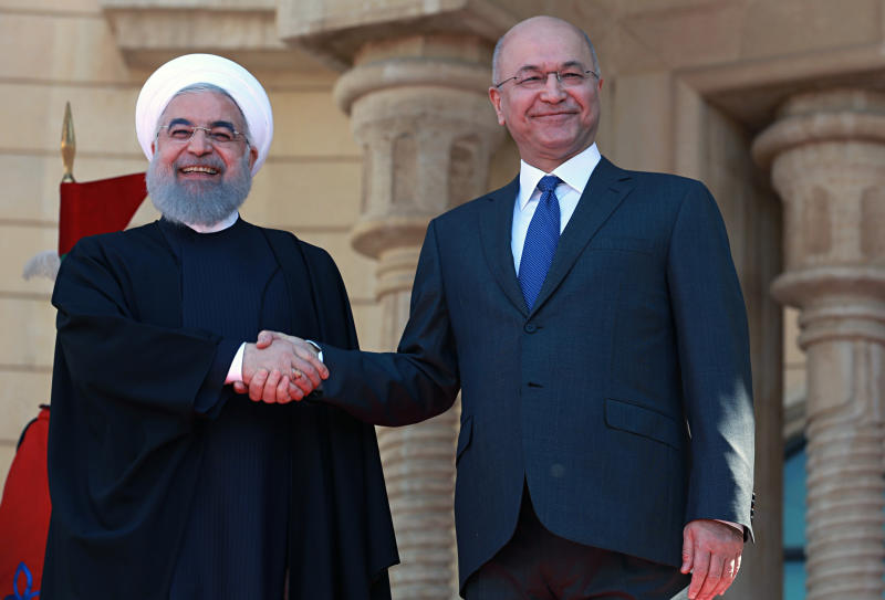 Iraqi President Barham Salih, right, shakes hands with visiting Iranian President Hassan Rouhani, at Salam Palace in Baghdad, Iraq, Monday, March 11, 2019. Iranian President Hassan Rouhani arrived in Baghdad on Monday, making his first official visit to the nation that Tehran once fought a bloody war against. (AP Photo/Khalid Mohammed)