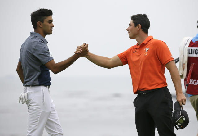 Viktor Hovland, right, of Norway, is greeted by Devon Bling, left, on the 18th green of the Pebble Beach Golf Links during the final round of the USGA Amateur Golf Championship Sunday, Aug. 19, 2018, in Pebble Beach, Calif. (AP Photo/Eric Risberg)