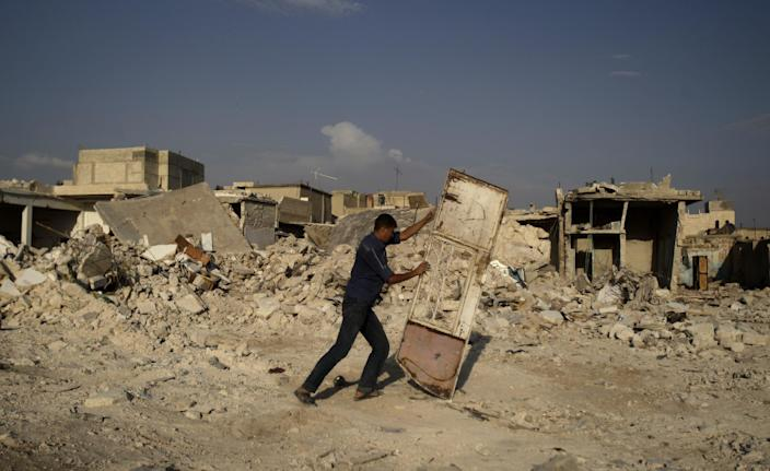 A Syrian man pushes a door away from the rubble of houses destroyed in a government airstrike, in the Syrian town of Azaz, on the outskirts of Aleppo, Friday, Aug. 31, 2012. (AP Photo/Muhammed Muheisen)