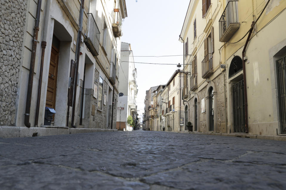 An empty street in Fondi, near Rome, Friday, March 20, 2020. Fondi, a farm town which has the largest wholesale produce market serving Rome and Naples has been put under even more stringent lockdown than the rest of the country due to a cluster of COVID-19 cases. For most people, the new coronavirus causes only mild or moderate symptoms. For some it can cause more severe illness. (AP Photo/Andrew Medichini)