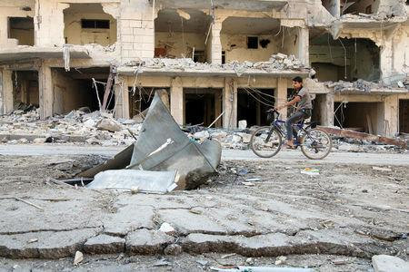 A man rides a bicycle near damaged ground in the rebel held besieged al-Sukkari neighbourhood of Aleppo