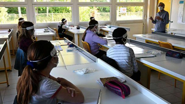 PHOTO: Schoolchildren wearing protective mouth masks and face shields listen to their teacher in a classroom at Claude Debussy college in Angers, France, May 18, 2020. (Damien Meyer/AFP via Getty Images)