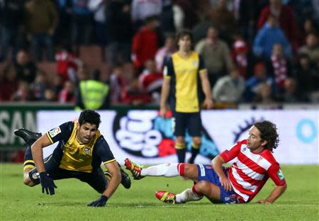 Atletico Madrid's Diego Costa (L) falls on the pitch next to Granada's Manuel Rolando Iturra during their Spanish First Division soccer match at Nuevo Los Carmenes stadium in Granada October 31, 2013. REUTERS/Pepe Marin