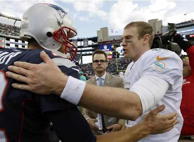 New England Patriots quarterback Tom Brady, left, and Miami Dolphins quarterback Ryan Tannehill, right, speak at midfield after an NFL football game on Sunday, Oct. 27, 2013, in Foxborough, Mass. The Patriots won 27-17. (AP Photo/Steven Senne)