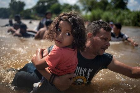"Luis Acosta holds 5-year-old Angel Jesus, both from Honduras, as a caravan of migrants from Central America en route to the United States crossed through the Suchiate River into Mexico from Guatemala in Ciudad Hidalgo, Mexico, October 29, 2018. Adrees Latif: ""For the past nine days, I had been following a caravan of over 7,000 migrants from Central America who were making their way north after crossing the Guatemala-Mexico border. Instead of trying to attempt another gate crossing, the migrants had moved towards the Suchiate River to try to cross. Most of the migrants had already made it to the Mexican side of the river and were resting and drying their clothes along the bank. In the river, dozens of migrant men had locked arms to make a snake-like human cordon from the Guatemalan side to Mexico, so no-one would get swept by its powerful pull. With one camera in hand and a 35 mm lens, I broke into the cordon to photograph the last group of migrants crossing. A family that had made it to the middle of the river was handing their children to other men to help them reach the shore. As a man grabbed the girl in front of me, I followed him, photographing, as he carried her to safety. Moments later, the last set of migrants crossed, and the men who had locked hands in the cordon all swam towards Mexico and started celebrating that the caravan had made it. This photograph begs the question: why would a family leave home and not only risk their own lives but also the lives of their children by doing such extraordinary things? What propels someone to walk without knowing where they will next break bread or quench their thirst? It also reminds me of the poem ""Home"" by Warsan Shire that starts: ""No one leaves home unless home is the mouth of a shark."" REUTERS/Adrees Latif/File photo"