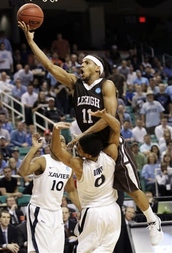 Lehigh's Mackey McKnight (11) drives into Xavier's Dee Davis (0) during the second half of a third-round NCAA tournament college basketball game in Greensboro, N.C., Sunday, March 18, 2012. (AP Photo/Chuck Burton)
