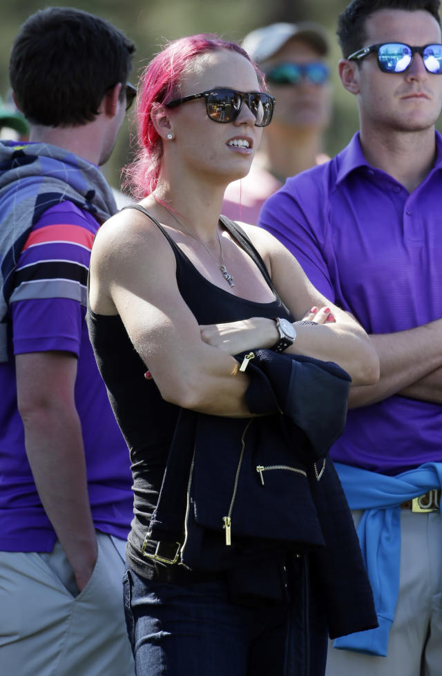 Tennis player Caroline Wozniacki watches her fiancee Rory McIlroy, of Northern Ireland, during the first round of the Masters golf tournament Thursday, April 10, 2014, in Augusta, Ga. (AP Photo/Darron Cummings)