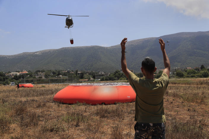 A Lebanese soldier directs an army helicopter as it arrives to refill a tank with water to extinguish a forest fire, at Qobayat village, in the northern Akkar province, Lebanon, Thursday, July 29, 2021. Lebanese firefighters are struggling for the second day to contain wildfires in the country's north that have spread across the border into Syria, civil defense officials in both countries said Thursday. (AP Photo/Hussein Malla)