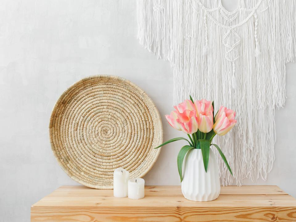 White ceramic vase, bouquet of pink tulip flowers, wicker tray, candles, and macrame