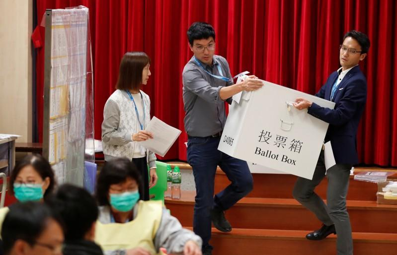 Polling officials carry a ballot box to count the votes of the Hong Kong council elections, in a polling station in Hong Kong