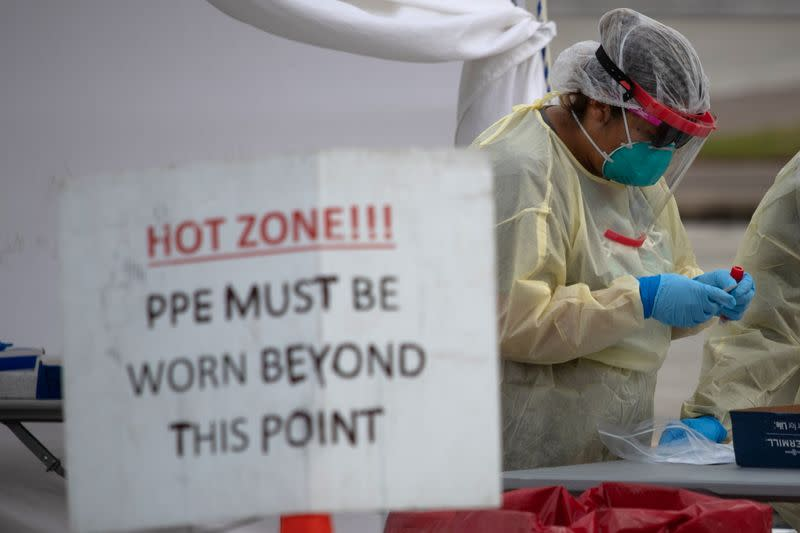 FILE PHOTO: A healthcare worker prepares specimen collection tubes at a coronavirus disease (COVID-19) drive-thru testing location in Houston