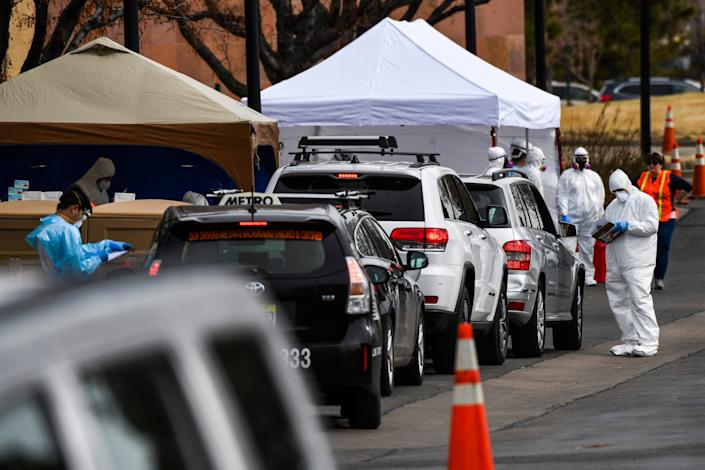 Healthcare workers from the Colorado Department of Public Health and Environment test a long line of people for COVID-19 at the state's first drive-up testing center on March 12, 2020 in Denver, Colorado.