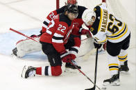 New Jersey Devils defenseman Ryan Murray (22) tries to keep Boston Bruins left wing Brad Marchand (63) from the puck in front of Devils goaltender Mackenzie Blackwood (29) during the first period of an NHL hockey game, Tuesday, May 4, 2021, in Newark, N.J. (AP Photo/Kathy Willens)