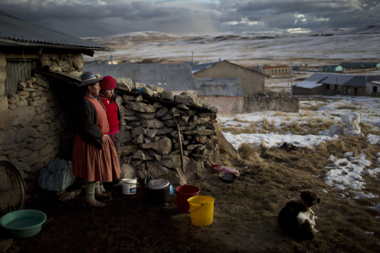 <p>Rosa Carcabusto and her daughter Maria Luque stand outside their home before cooking a dinner soup of wheat and dried potatoes, in San Antonio de Putina in the Puno region of Peru. Poverty has driven many farmers' children from their homes to work in illegal mines or Peru's flourishing cocaine trade. (AP Photo/Rodrigo Abd)</p>