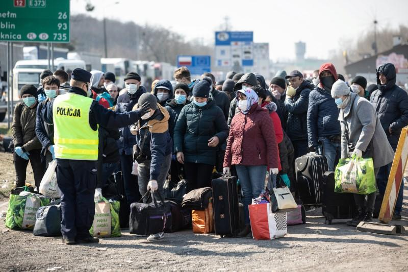 People queue to cross to Ukraine at the border crossing in Dorohusk