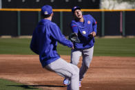 Chicago Cubs' Anthony Rizzo, right, tosses the ball to a pitcher during the team's spring training baseball workout in Mesa, Ariz., Monday, Feb. 22, 2021. (AP Photo/Jae C. Hong)