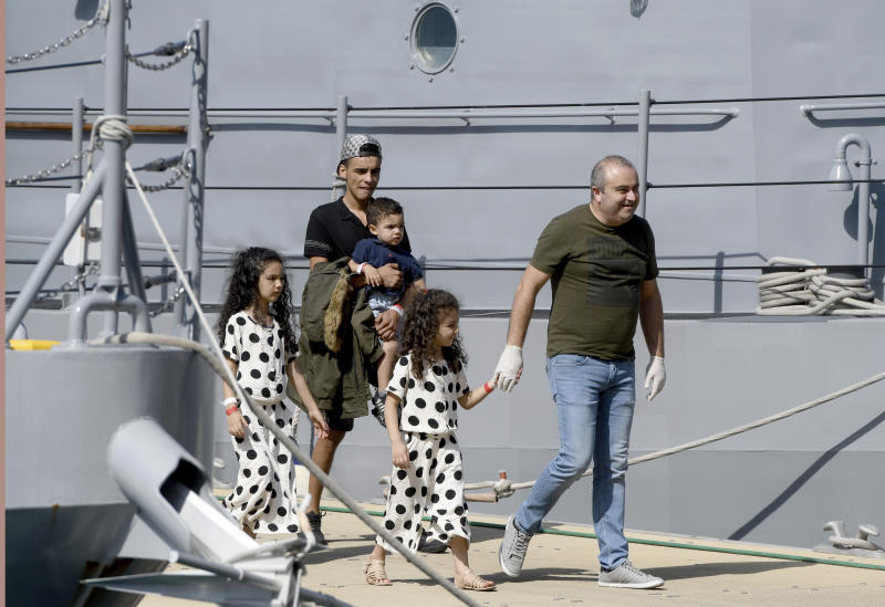 A family is assisted as it disembarks from a Maltese naval vessel in the port of La Valletta in Malta after being transferred from a humanitarian ship which rescued them at sea over a week ago, Sunday, Sept. 30, 2018. The Maltese government said Sunday that the migrants would be then transferred in the coming days to the four countries agreeing to accept them: France, Germany, Spain and Portugal. (AP Photo/Jonathan Borg)