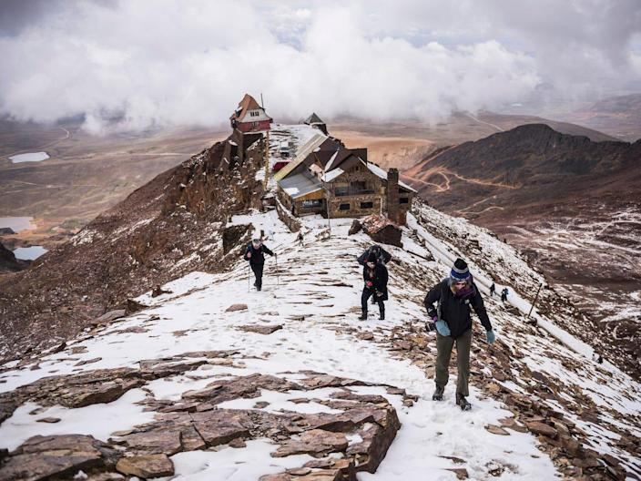 tourists climb up from the abandoned ski resort in bolivia