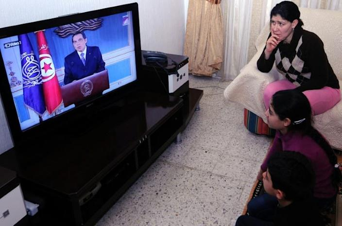 A Tunisian family watches TV on January 13, 2011 as Zine El-Abidine Ben Ali resigns as president (AFP Photo/Fethi Belaid)