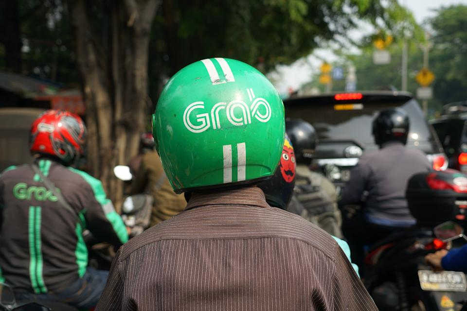 Jakarta, Indonesia - May 2 2018: Bike passengers wearing Helmet with Grab Logo. Grab is a technology company that offers wide range of ride-hailing and logistics services through its app in Southeast A