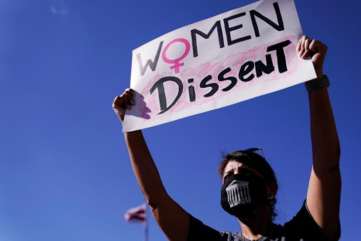 """A woman holding up a sign that says """"Women dissent"""" Erin Scott/Reuters"""
