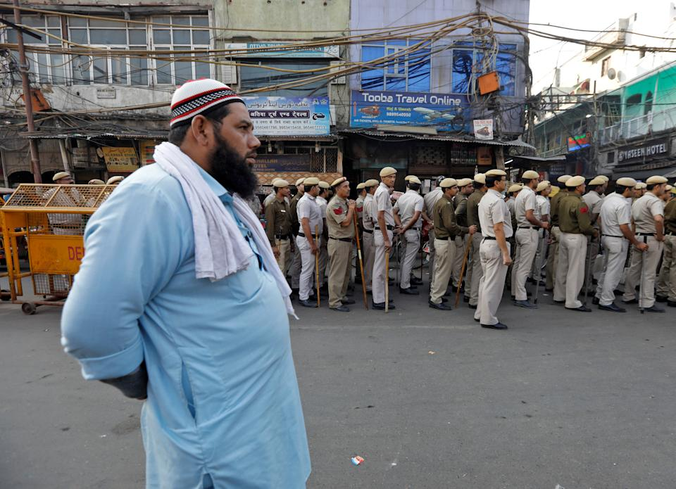 A Muslim man looks on as police officers conduct a flag march in a street outside Jama Masjid, before Supreme Court's verdict on a disputed religious site claimed by both majority Hindus and Muslim in Ayodhya, in the old quarters of Delhi, India, November 9, 2019. REUTERS/Adnan Abidi