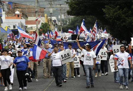Supporters of Norman Quijano, presidential candidate of the conservative Nationalist Republican Alliance party (ARENA), march during a protest regarding alleged electoral fraud near the Supreme Electoral Court in San Salvador March 11, 2014. REUTERS/Henry Romero