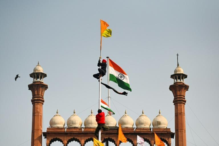 Protesters climb a flagpole at the ramparts of the Red Fort on January 26, 2021