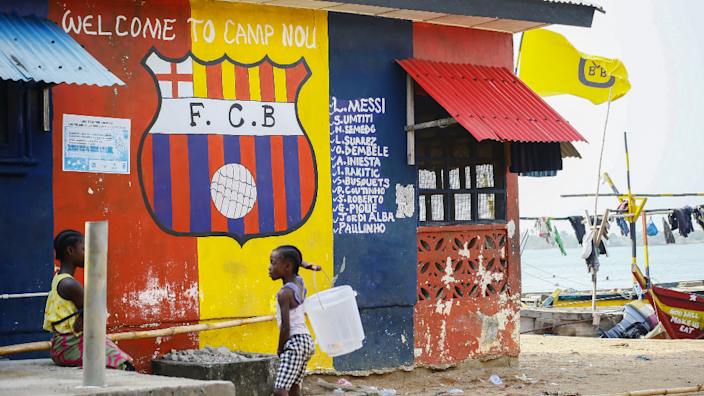 Children in front of building painted in the colours of Barcelona football club in FC Barcelona compound of Fanti town near Robertsport in Grand Cape Mount County, Liberia - Saturday 20 March 2021