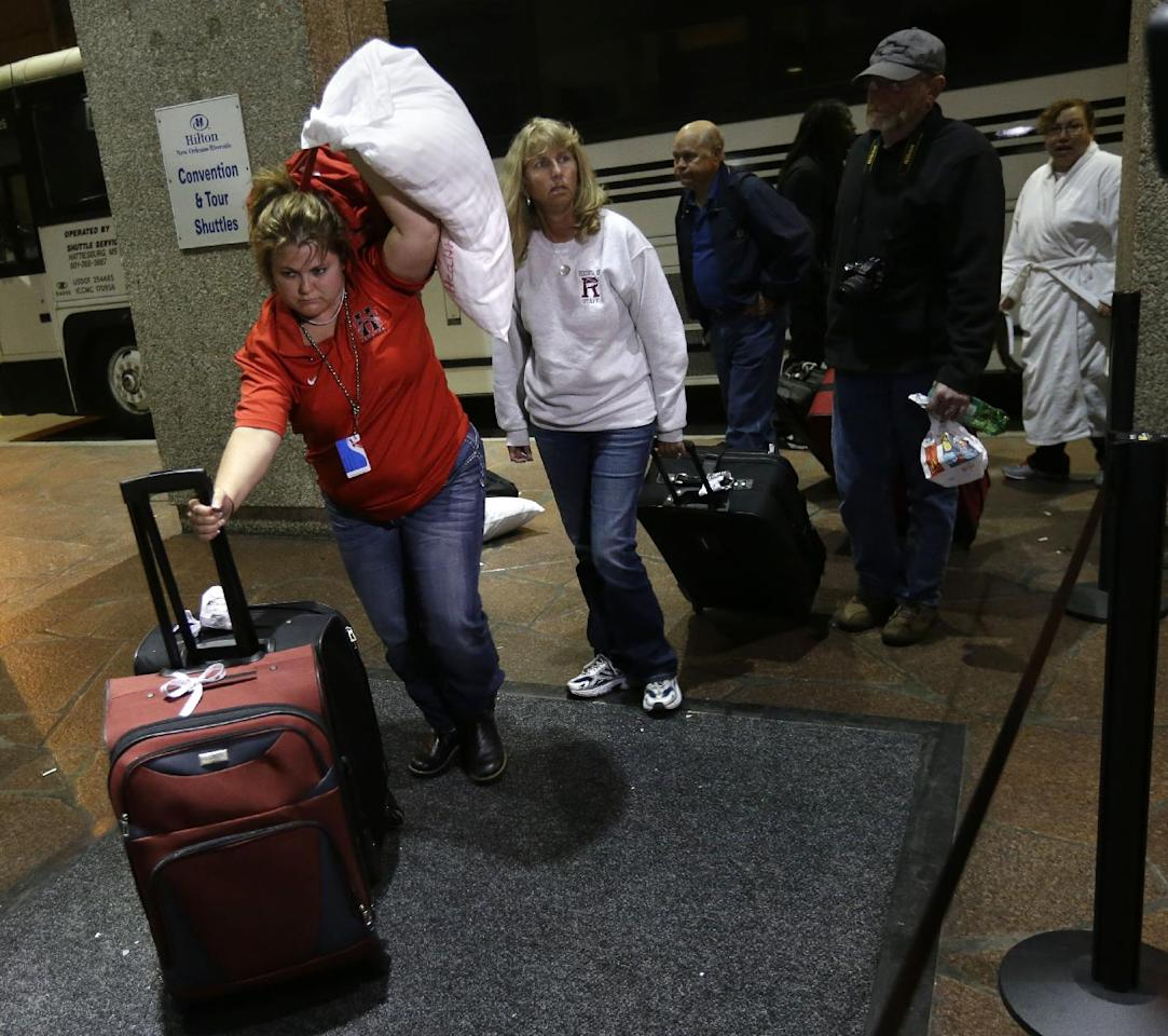 Passengers from the disabled Carnival Triumph cruise ship arrive by bus at the Hilton Riverside Hotel in New Orleans, Friday, Feb. 15, 2013. The ship had been idled for nearly a week in the Gulf of Mexico following an engine room fire. (AP Photo/Gerald Herbert)